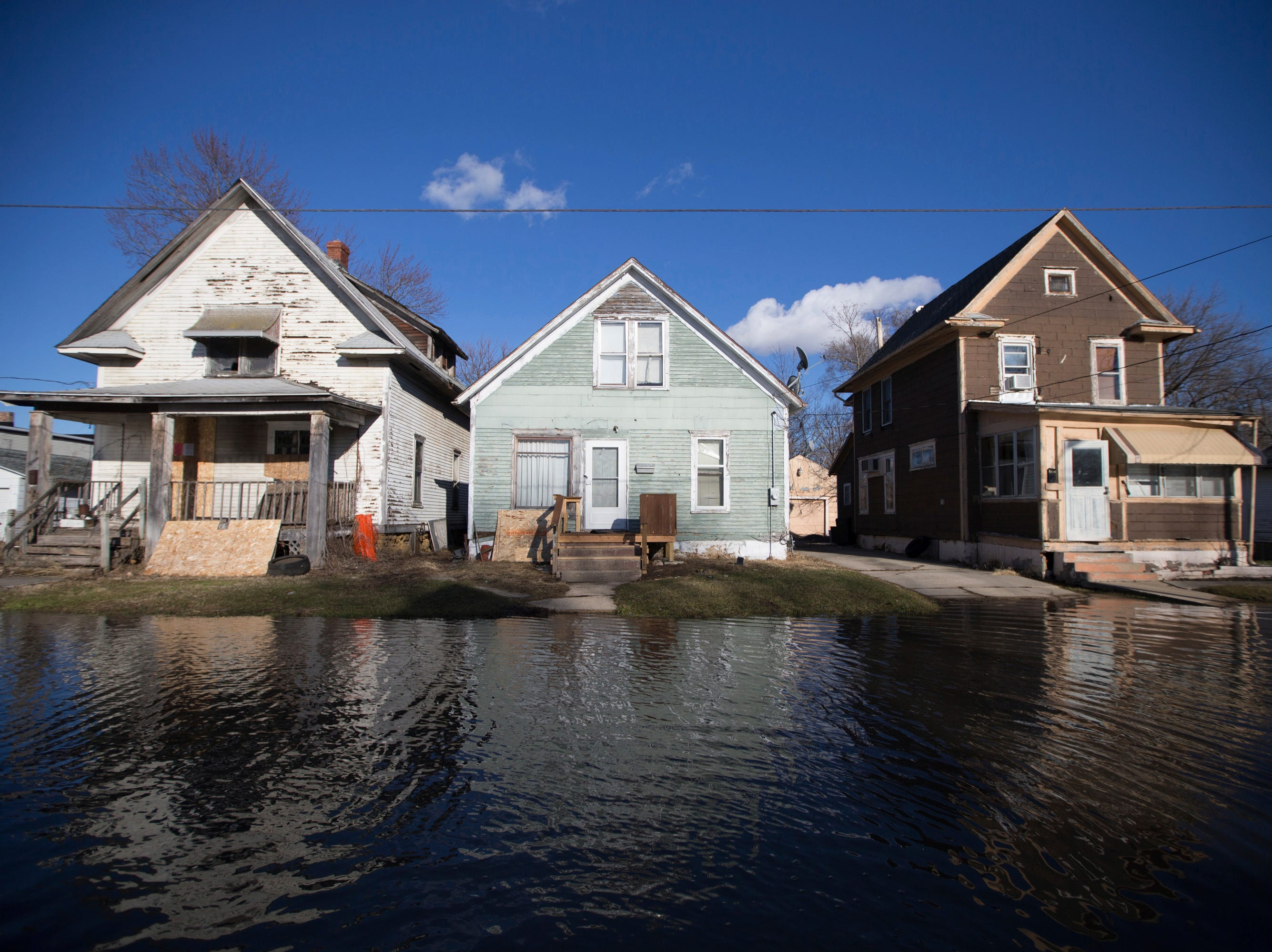 Floodwaters lap close to the front yards of homes on Friday, March 15, 2019, in Freeport, Ill. Rising waters along the Pecatonica and Rock rivers have flooded homes in northern Illinois.