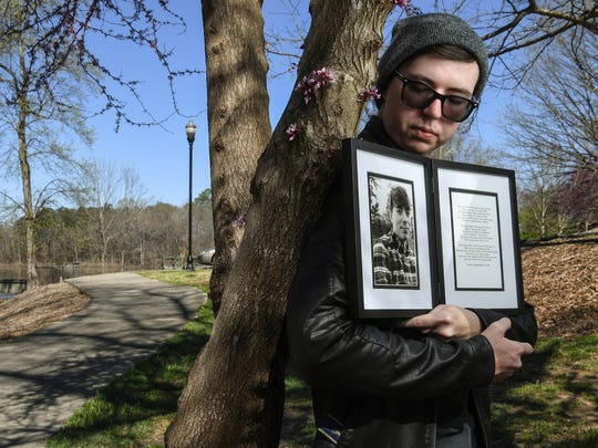 Andrew Phelps holds a photo and poem for his brother Thomas Phelps in Clemson.