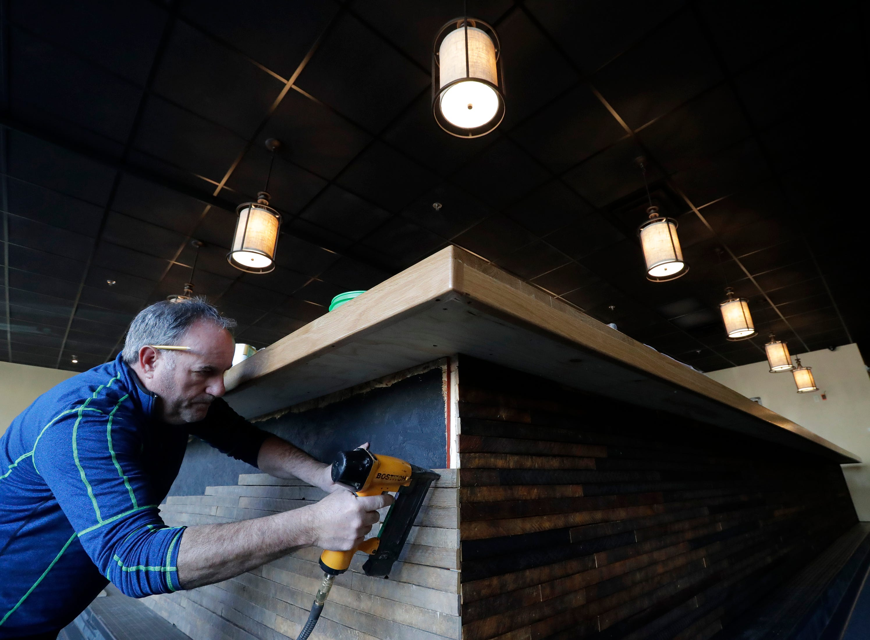 Owner Steve VanFossen installs reclaimed tobacco board on the front of the bar facade at the new Fress restaurant located at 511 W College Avenue in the space of the former Katsu-Ya Monday, March 12, 2019, in downtown Appleton, Wis. Dan Powers/USA TODAY NETWORK-Wisconsin