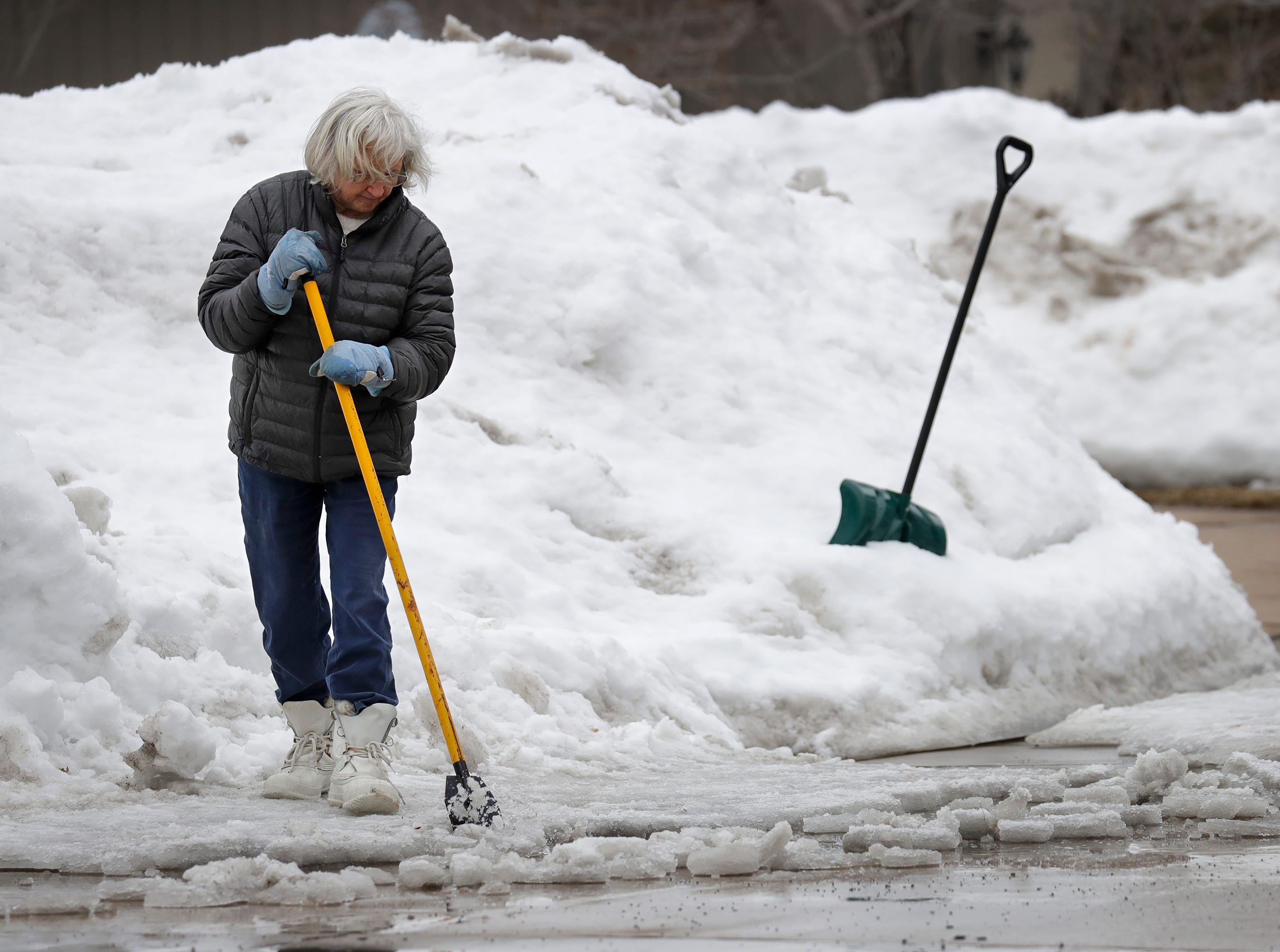 Kayleen Coburn is surrounded by large snowbanks as she breaks up thick ice to clear the entrance to her driveway along N. McDonald Street Monday, March 12, 2019, in Appleton, Wis. Dan Powers/USA TODAY NETWORK-Wisconsin