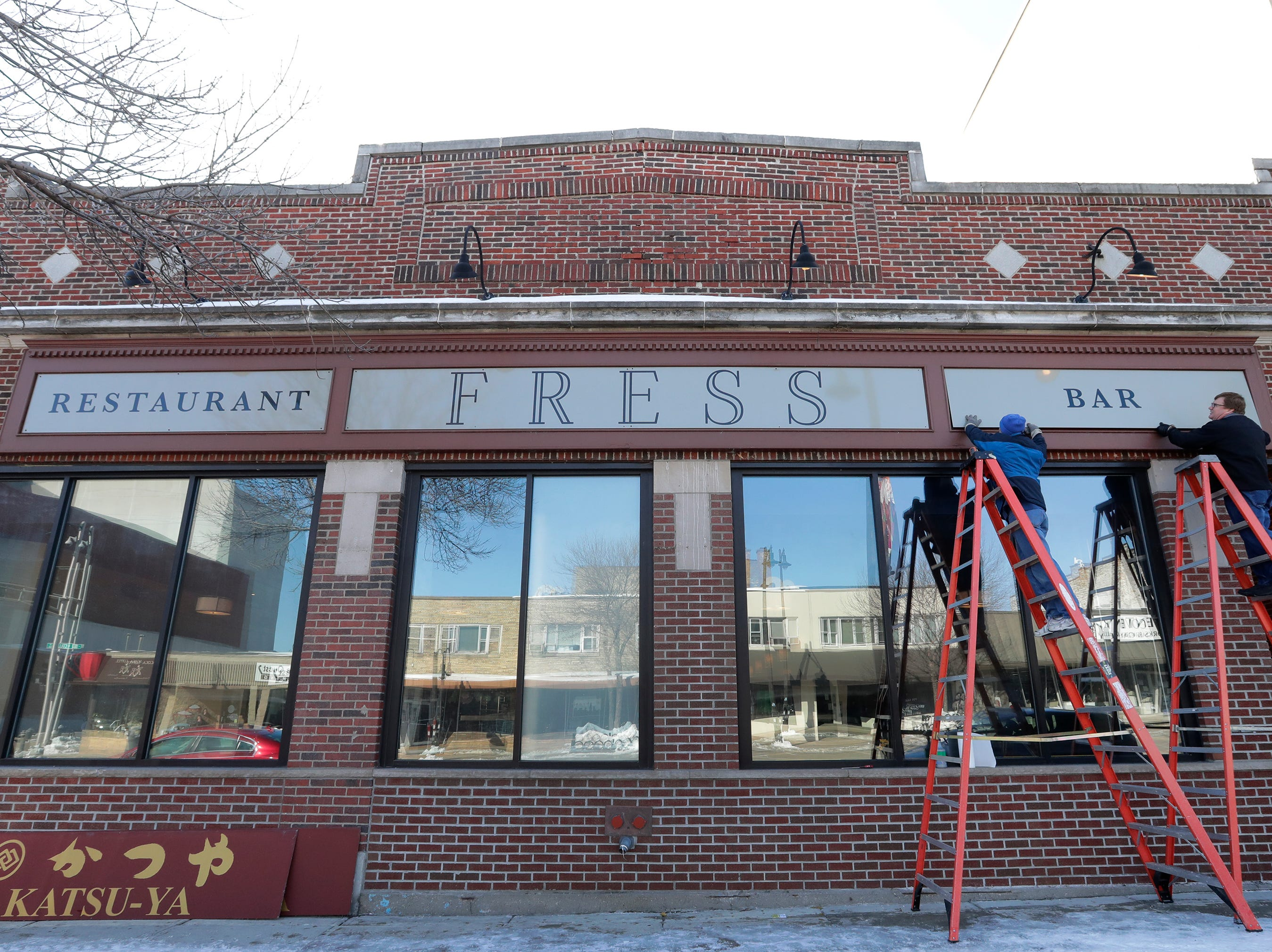 Employee Dane DeValk, left, collaborates with Eagle Sign & Design owner Chris Hermann to install the new Fress restaurant and bar sign at 511 W College Avenue in the space of the former Katsu-Ya Monday, March 12, 2019, in downtown Appleton, Wis. Dan Powers/USA TODAY NETWORK-Wisconsin