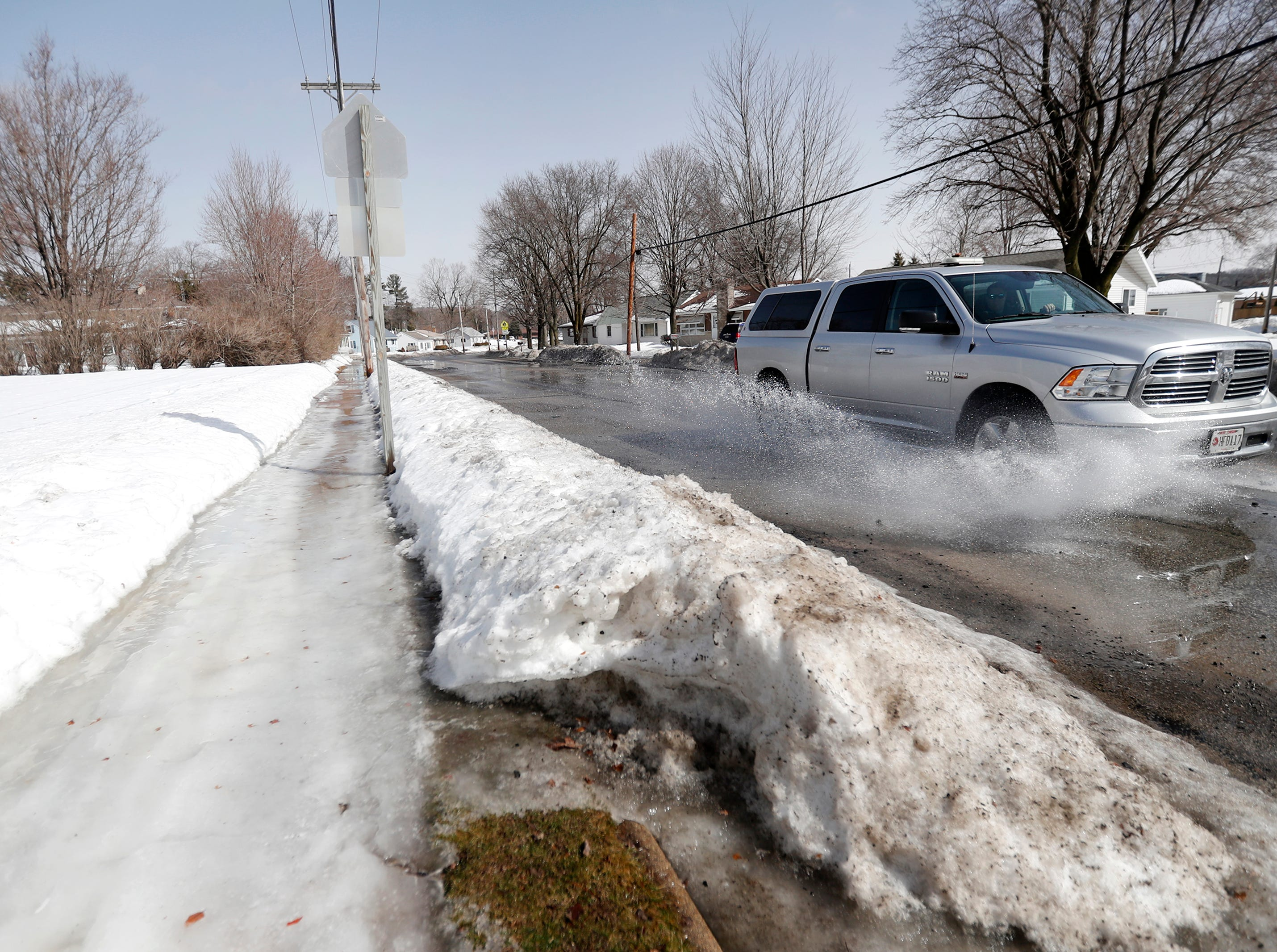 A motorist drives through water and pot holes along North Nash Street Thursday, March 14, 2019, in Hortonville, Wis. Danny Damiani/USA TODAY NETWORK-Wisconsin