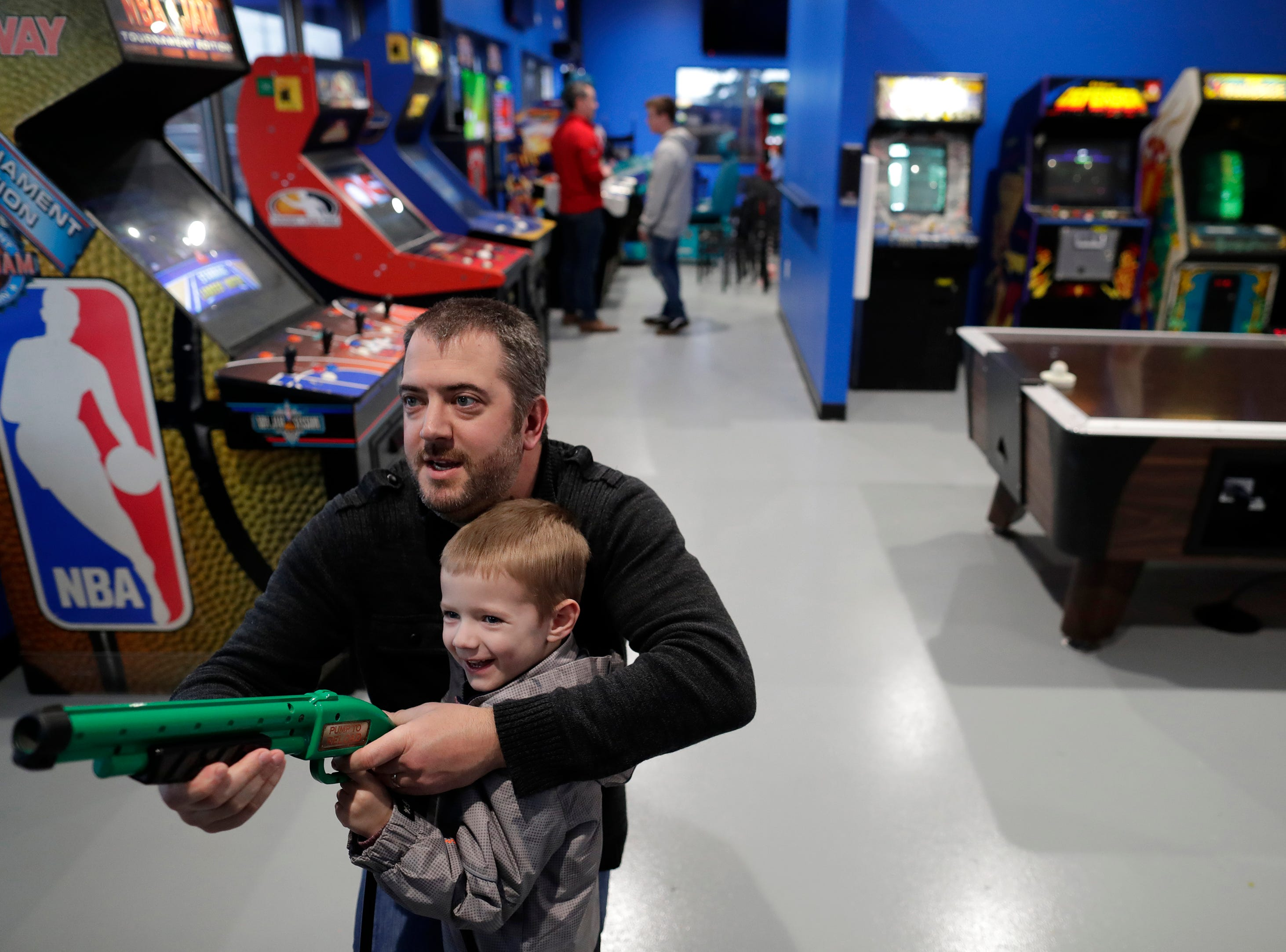 Aaron Mars and his son Caleb, 4, have fun playing the Big Buck World arcade game Thursday, March 14, 2019, at Pixel's Arcade & Sports Bar in Oshkosh, Wis. The two are from Oshkosh.Dan Powers/USA TODAY NETWORK-Wisconsin