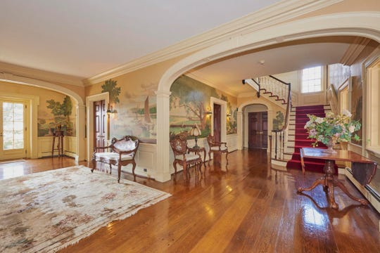 The grand foyer features an wonderfully  seafaring mural and custom door.