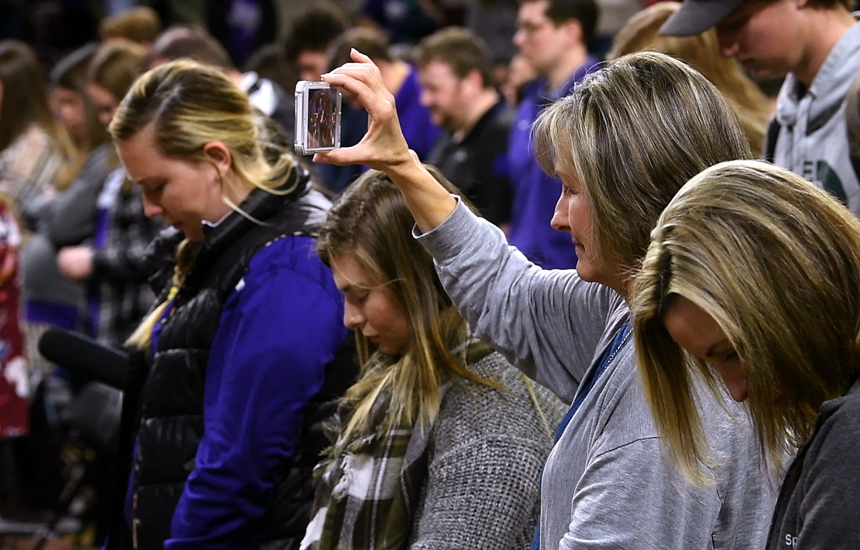 Audience members pray and record the moment during chapel Monday at Abilene Christian University's Moody Coliseum.