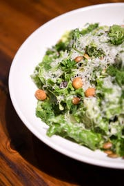 The romaine and arugula Caesar salad at Daphne at Twisted Laurel is topped with cilantro-lime caesar, masa croutons, toasted pepitas, herbs, pecorino and preserved lemon.