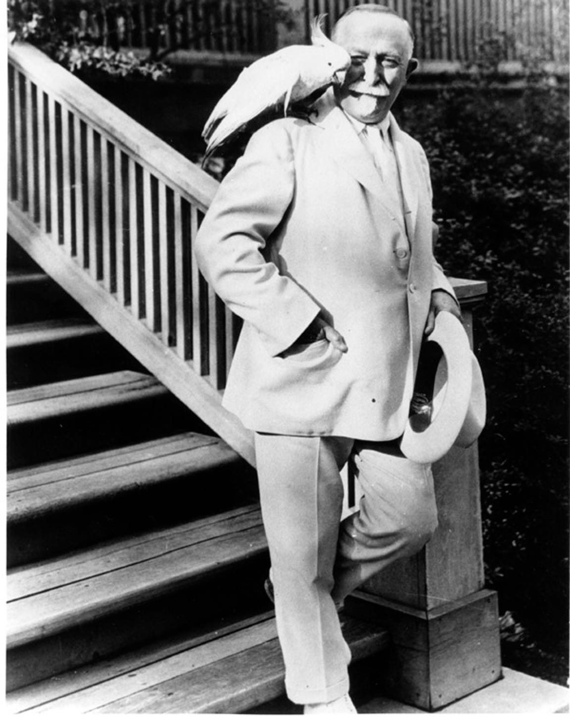 Dr. John Harvey Kellogg wearing his trademark all-white suit with his pet cockatoo on his shoulder.