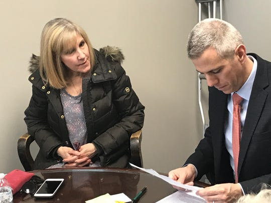 Laura Lutz shows Rep. Anthony Brindisi all of the promotional mailers, cards and other paperwork Spectrum has mailed her recently.