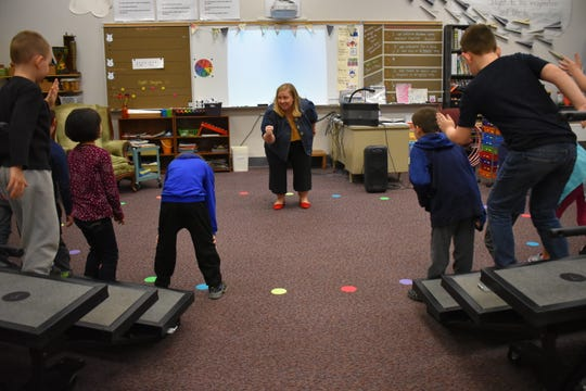 East Port Orchard Elementary music teacher Katie Olson sings with her class of second-grade students.
