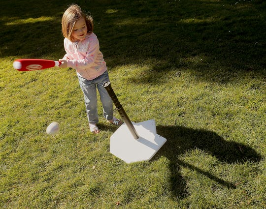 Natalie Voorhies, 3, bats with her T-ball set as she and her mother, Lisa, take advantage of the nice weather at Evergreen-Rotary Park in Bremerton on Monday.