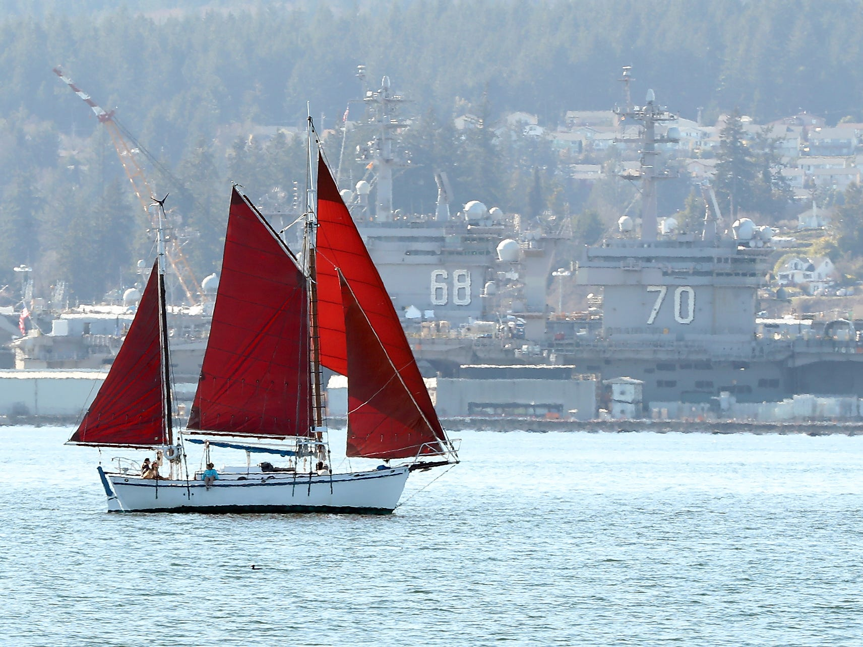 The vibrant red sails of a sailboat catch the breeze off of Naval Base Kitsap Bremerton on Monday, March 18, 2019.