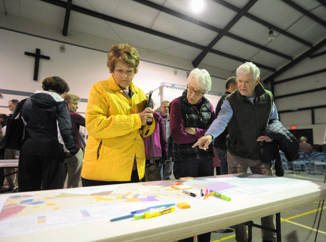 Alderman Maggie Tuttle, left, looks over a map that shows existing land uses on Blue Ridge Road, between the I-40 overpass and N.C. 9, before a small area plan input meeting on March 14.