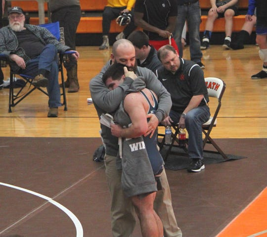 Dalton Metzger hugs his coach Dalton Moss after receiving his 100th career win during the Robin Drumm Classic in February of 2019.