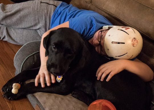 Andrew Yocum lays down with Loretta after extensively playing with her in the living room of his home. While Loretta's primary function is to help alert the family as to when he will have a seizure, she has quickly become one of Andrew's best friends and has helped give him a little bit of independence.
