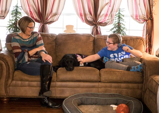 Benita Yocum and her son Andrew Yocum sit on the couch and play with their golden Labrador Loretta. Loretta has not only become the family pet and a companion for Andrew, who suffers from epilepsy, but her primary job is to alert them as to when Andrew will have a seizure. The Yocums were matched with Loretta in January of 2019 through 4 Paws for Ability, a nonprofit organization that places service dogs with those with disabilities.