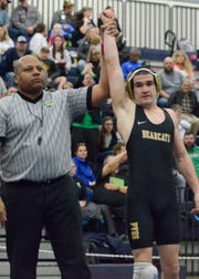 Adrian Salomone gets his hand raised after his 100th win against West Union's Chad Long during his first-round match during Division III sectionals at Blanchester High School.