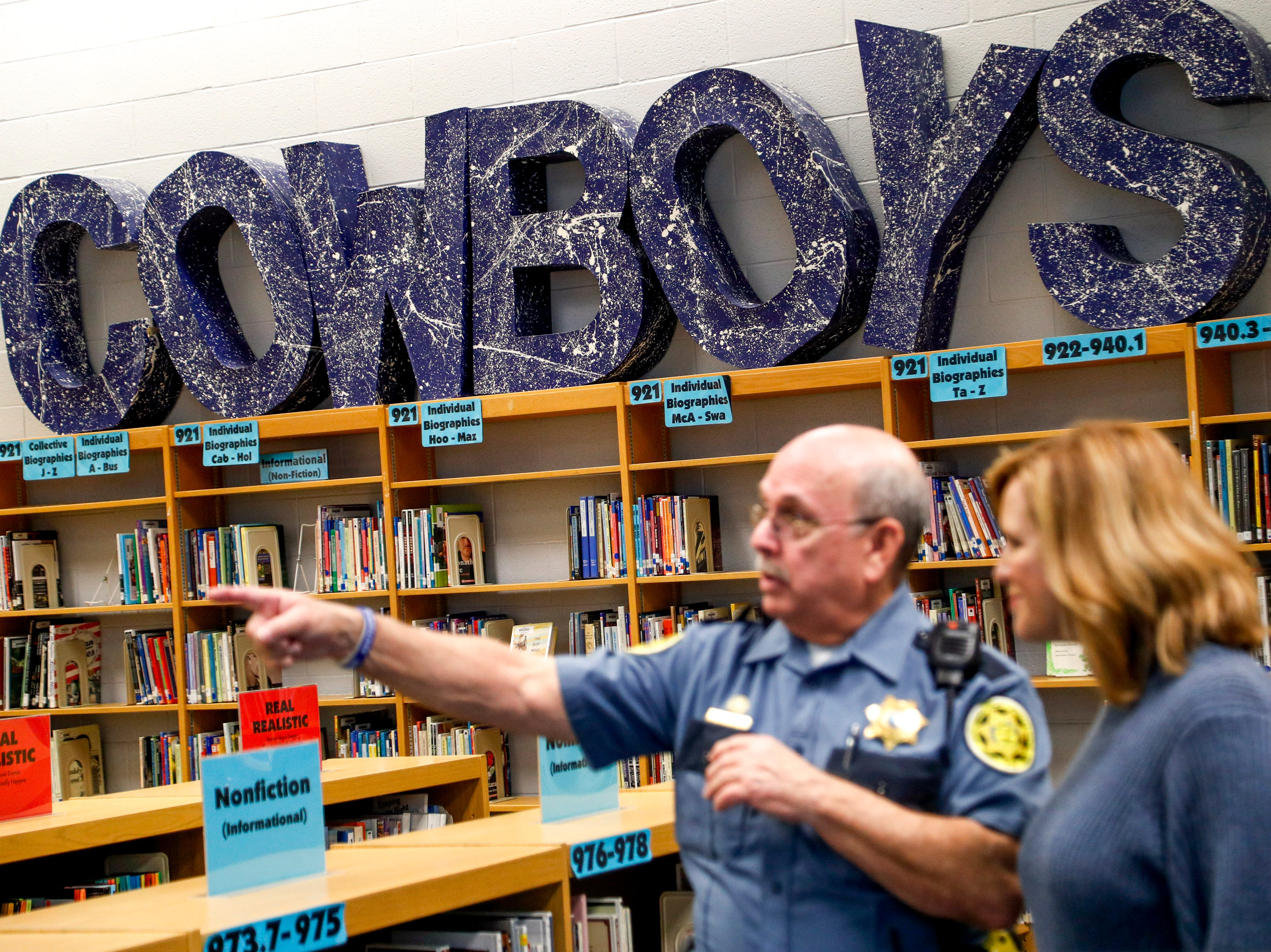 SRO Richard Brown speaks with principal Lisa Baker in the school library in front of shelves of books and a large letters for the school mascot at Richview Middle School in Clarksville, Tenn., on Friday, March 15, 2019.