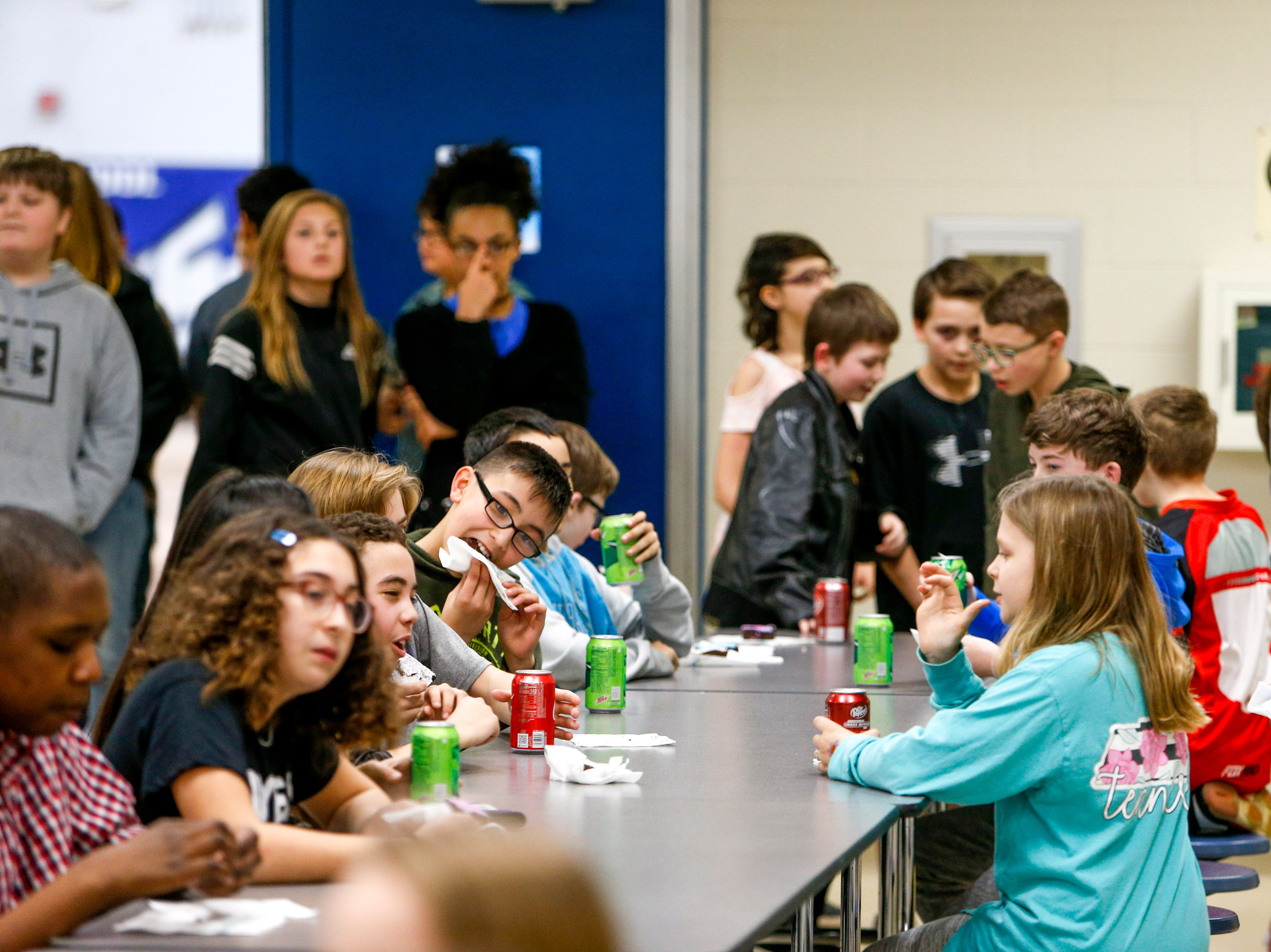 Students crowd the cafeteria tables during a break in classes where they can buy brownies at a bake sale put on by SRO Richard Brown, all proceeds will be donated to find the 8th grade dance at Richview Middle School in Clarksville, Tenn., on Friday, March 15, 2019.