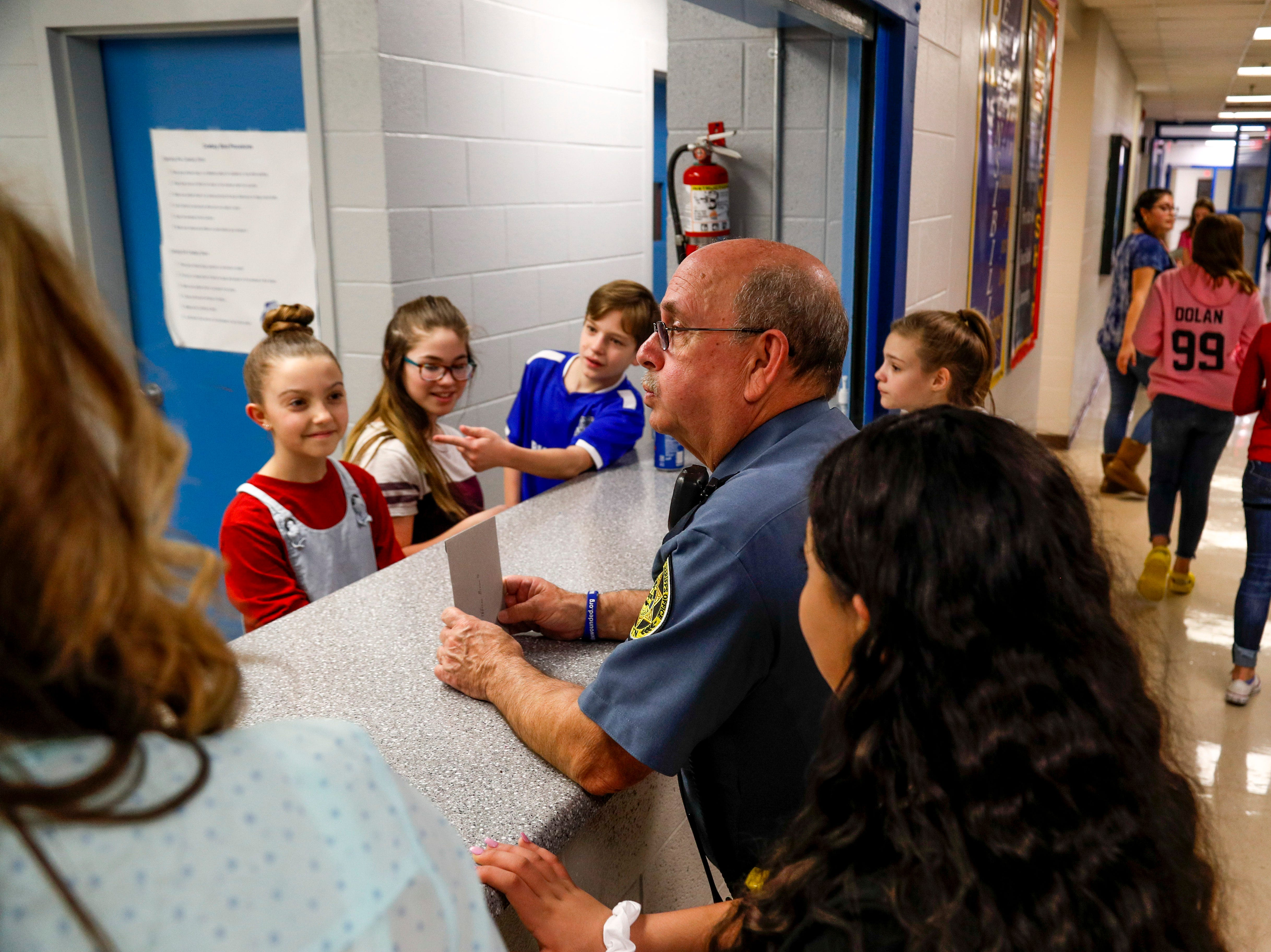 SRO Richard Brown leans over the counter and speaks with student helpers and others about the over 1200 brownies sold to help fund the 8th grade dance at Richview Middle School in Clarksville, Tenn., on Friday, March 15, 2019.