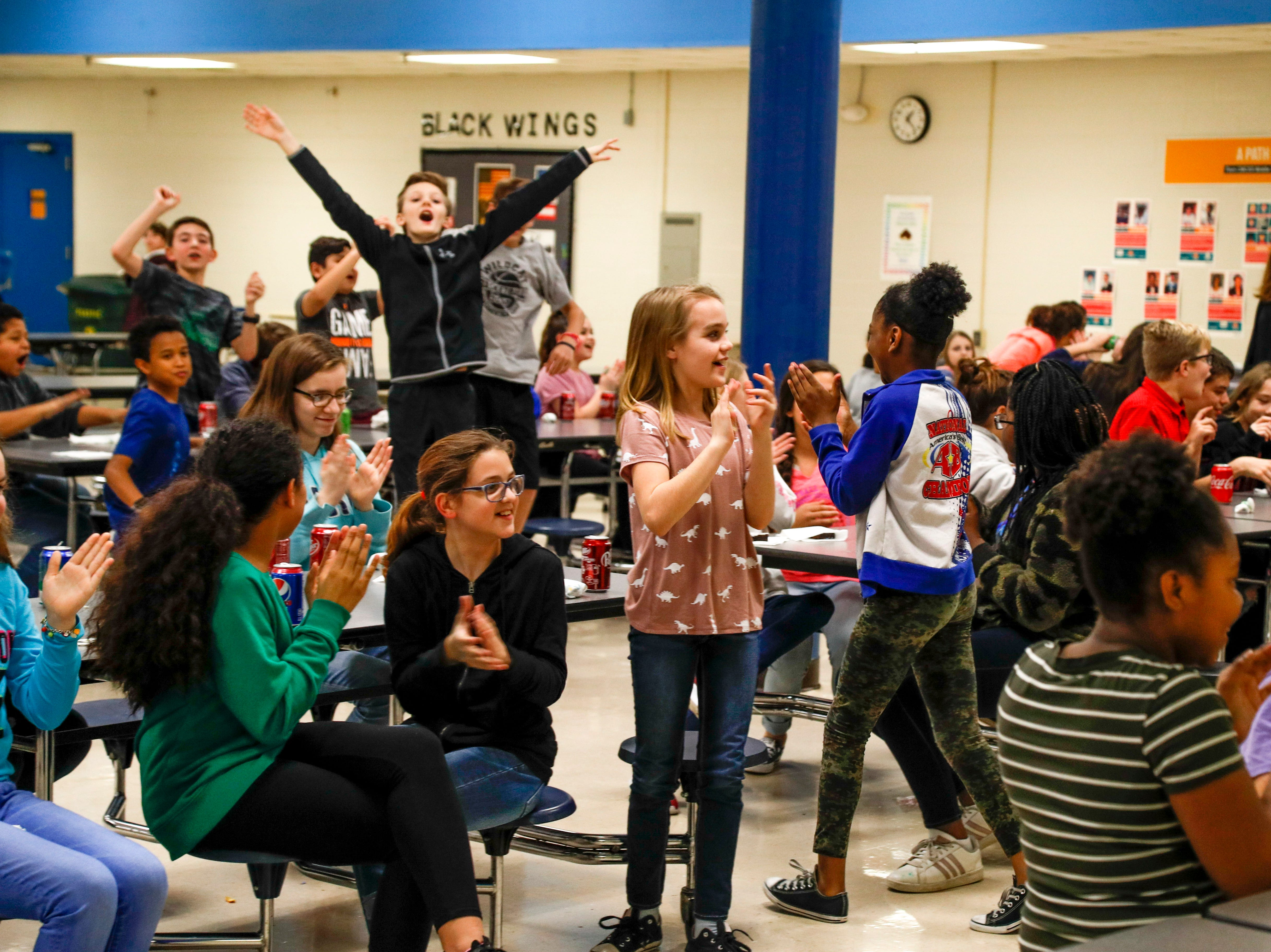 Students in the cafeteria clap and cheer for SRO Richard Brown after Brown finishes and interview and heads back to check inventory of brownies at Richview Middle School in Clarksville, Tenn., on Friday, March 15, 2019.