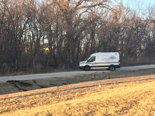 A crime scene investigation van pulls away from the area where police found a man's body Sunday evening north of Thomas Beck Road.