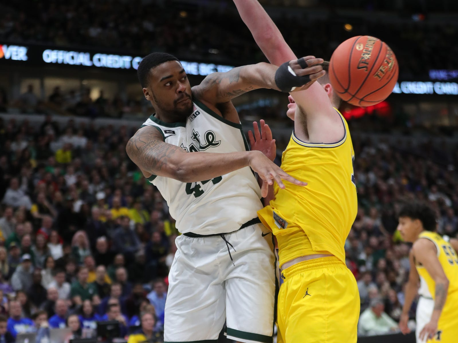 Michigan State's Nick Ward passes around Michigan's Jon Teske during Big Ten tournament championship Sunday, March 17, 2019 in Chicago.