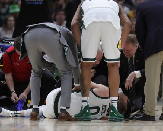 Michigan State coach Tom Izzo, right, talks to forward Kyle Ahrens who suffered a foot injury against Michigan in the Big Ten tournament championship Sunday, March 17, 2019 in Chicago.