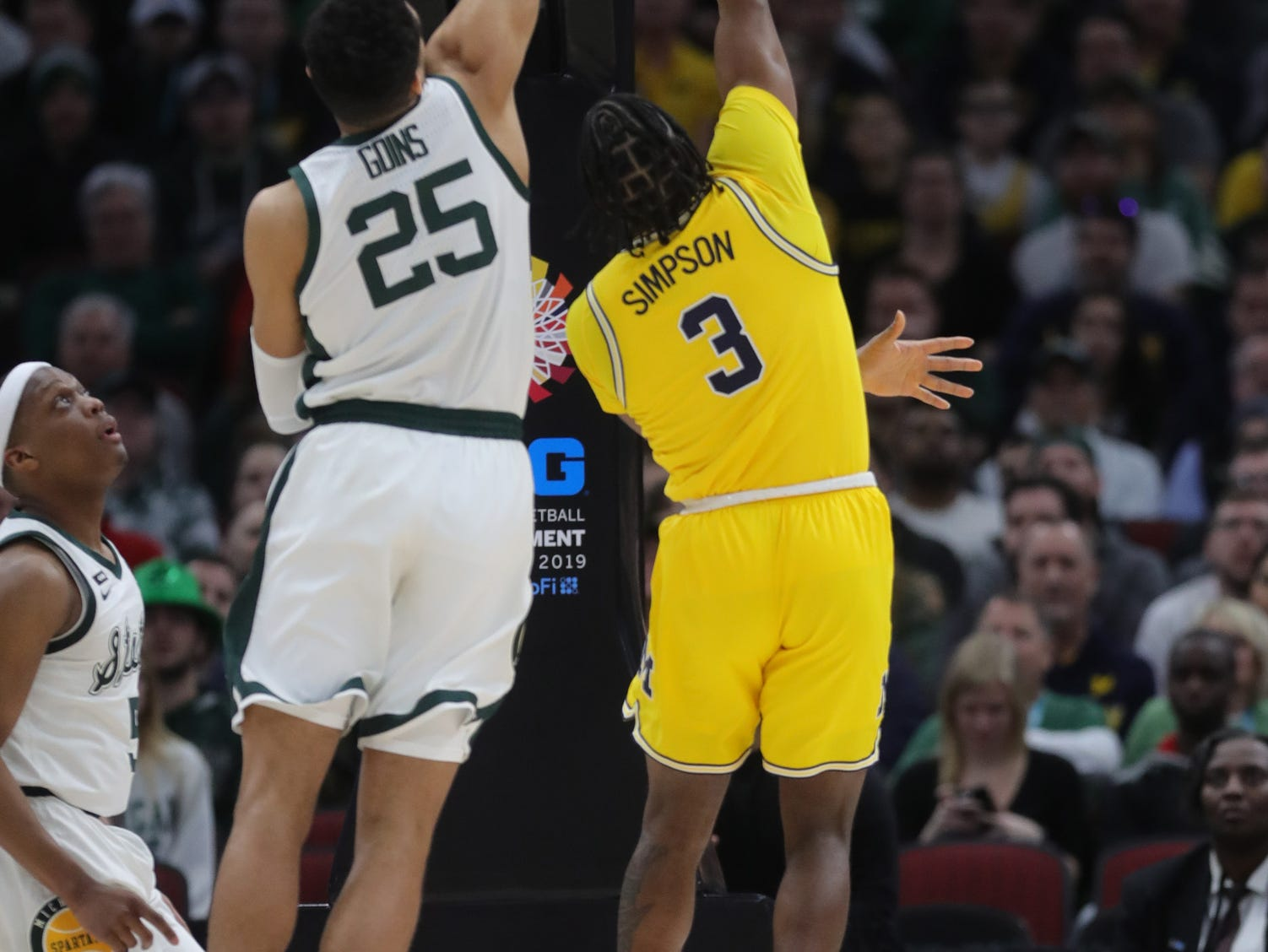 Michigan State's Kenny Goins blocks a shot by Michigan's Zavier Simpson during the first half of the Big Ten tournament championship Sunday, March 17, 2019 in Chicago.