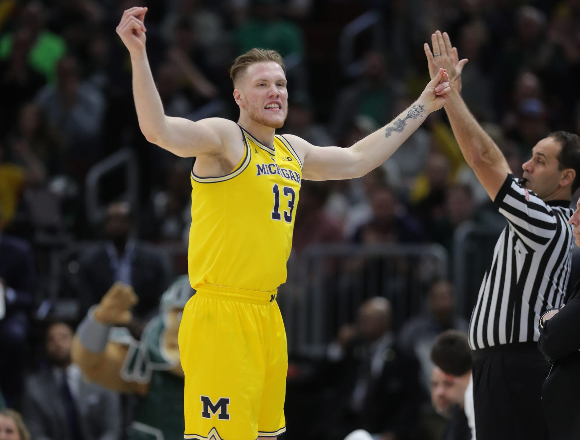 Michigan's Ignas Brazdeikis celebrates a 3-pointer against Michigan State during the first half of the Big Ten tournament championship Sunday, March 17, 2019 in Chicago.