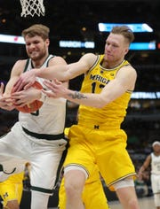 Michigan State's Kyle Ahrens fights for the rebound against Michigan's Ignas Brazdeikis during the first half of the Big Ten tournament championship Sunday, March 17, 2019 in Chicago.