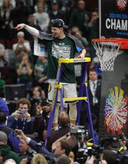 Michigan State's Matt McQuaid cuts the net after the 65-60 win against Michigan in the Big Ten tournament championship Sunday, March 17, 2019 in Chicago.