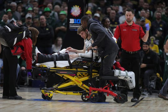Joshua Langford kisses teammate Kyle Ahrens as he is taken off the court with a foot injury Sunday in Chicago.