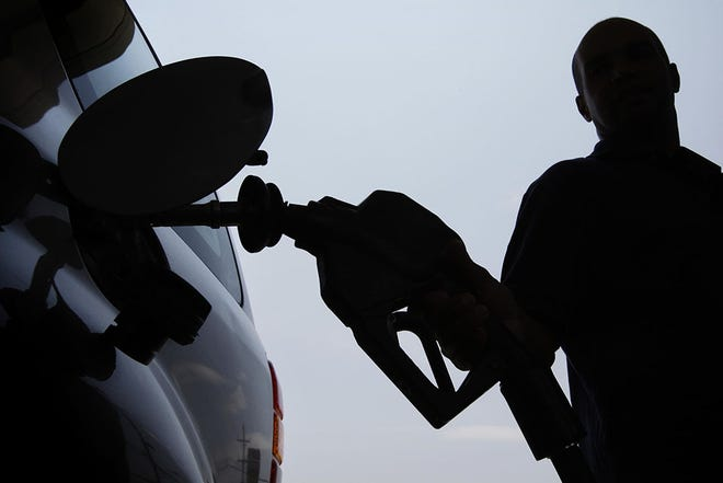 A person pulls a gas pump from his vehicle after filling his tank.