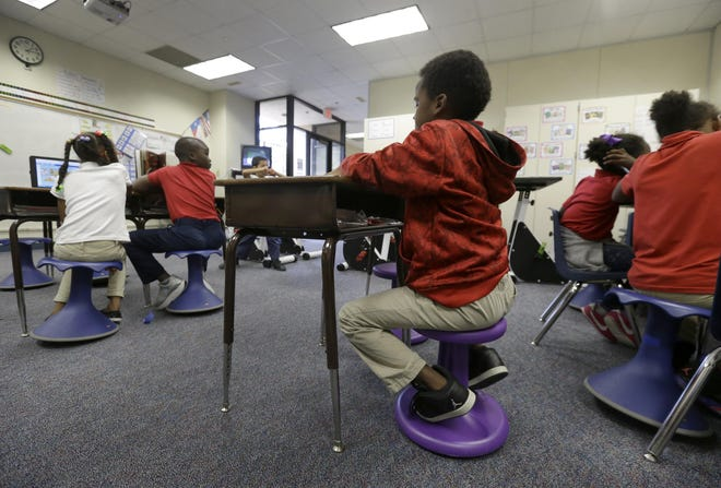 In this Thursday, Oct. 20, 2016 photo, third graders read as they sit on Hokki Stools in a classroom at Best Elementary, in Houston.