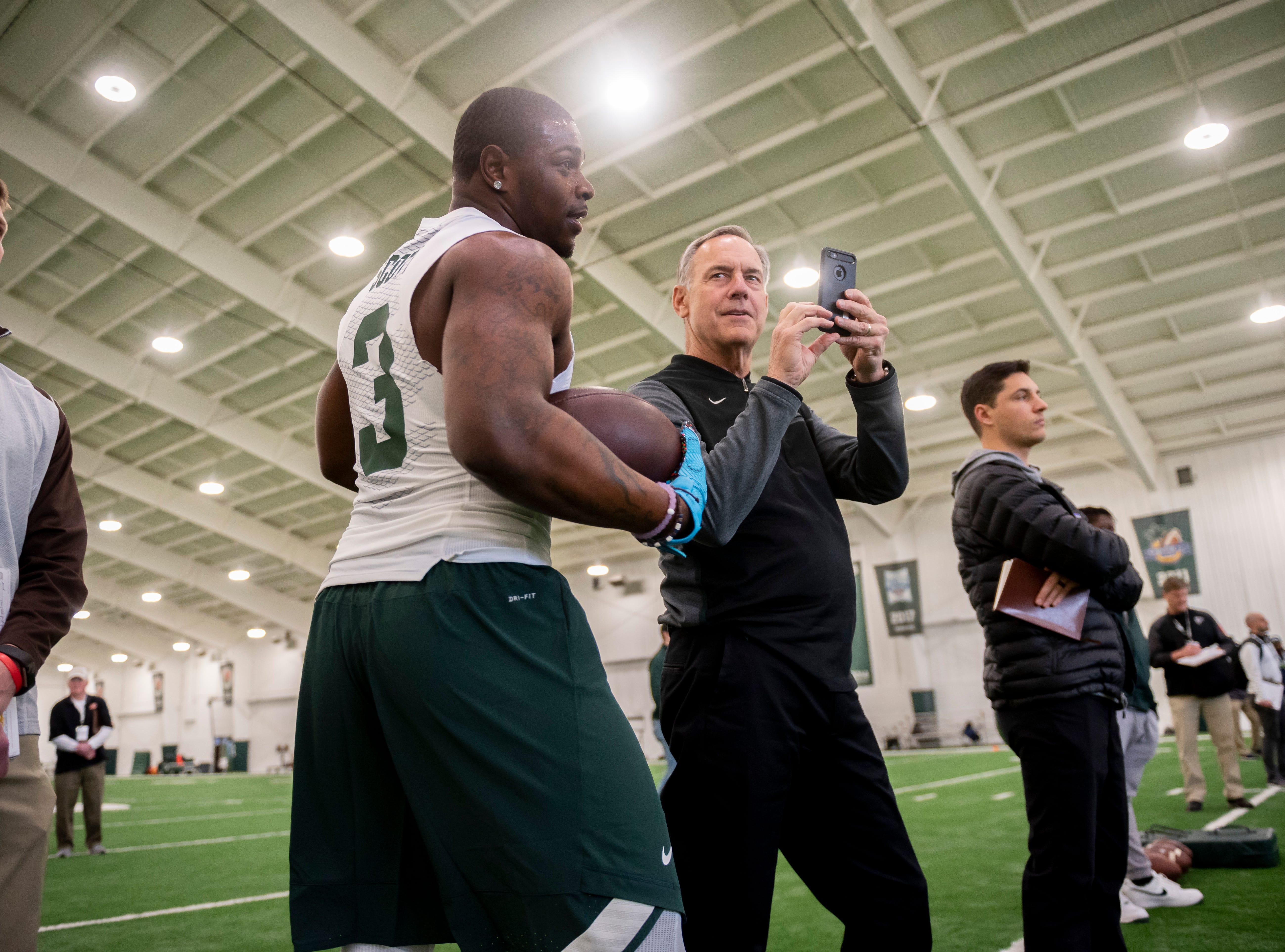 Michigan State head coach Mark Dantonio smirks at running back LJ Scott after Scott almost ran into Dantonio while running drills.