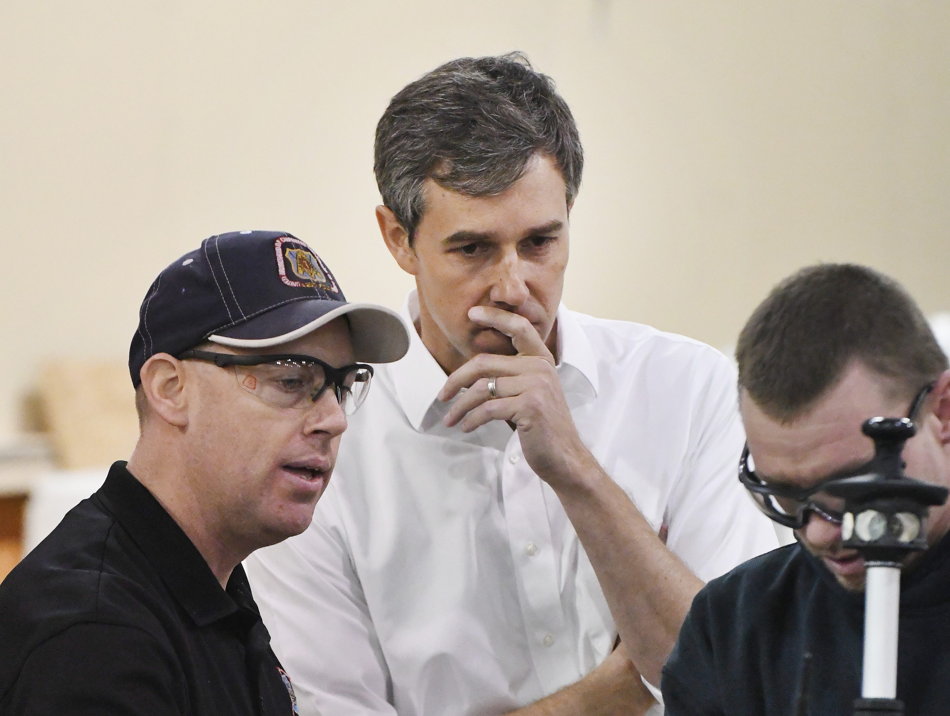 Instructor Andy Showers and student Josh Rice show Democratic U.S. presidential candidate Beto O'Rourke a carpentry device used in checking level during a tour of the Detroit Carpenters Training Center.
