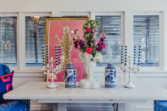 Tying the bright pink of a painting in with a fun floral arrangement brings the art into the room and creates a nice line for the eye. (Handout/TNS)