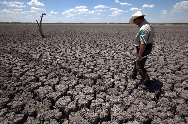 Texas State Park police officer Thomas Bigham walks across the cracked lake bed of O.C. Fisher Lake, in San Angelo, Texas, on Aug. 3, 2011. The impacts of record-breaking heat and years of low or no rainfall can be felt years after a dry spell passes.