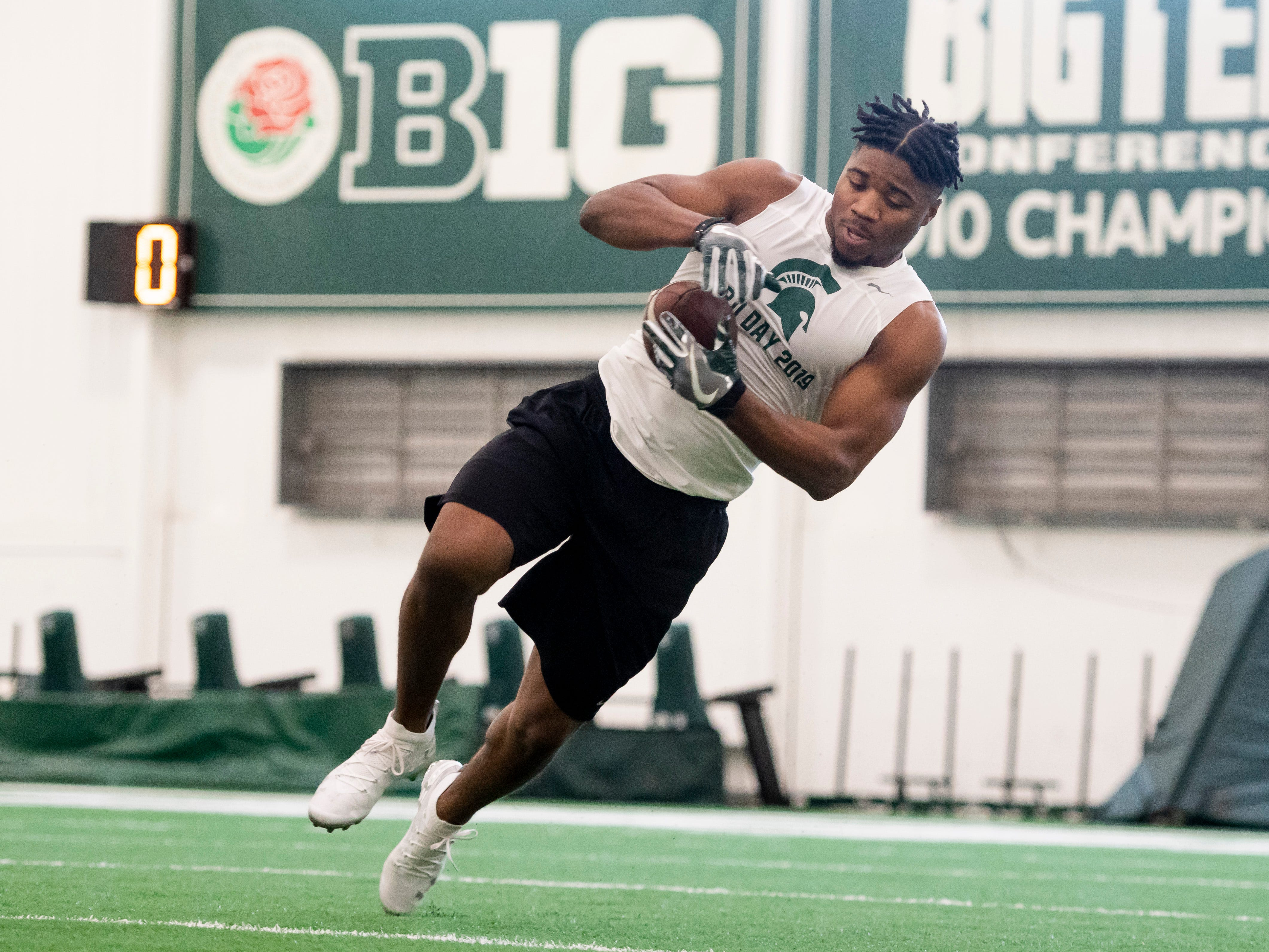 Michigan State linebacker Andrew Dowell catches a pass while running a drill.
