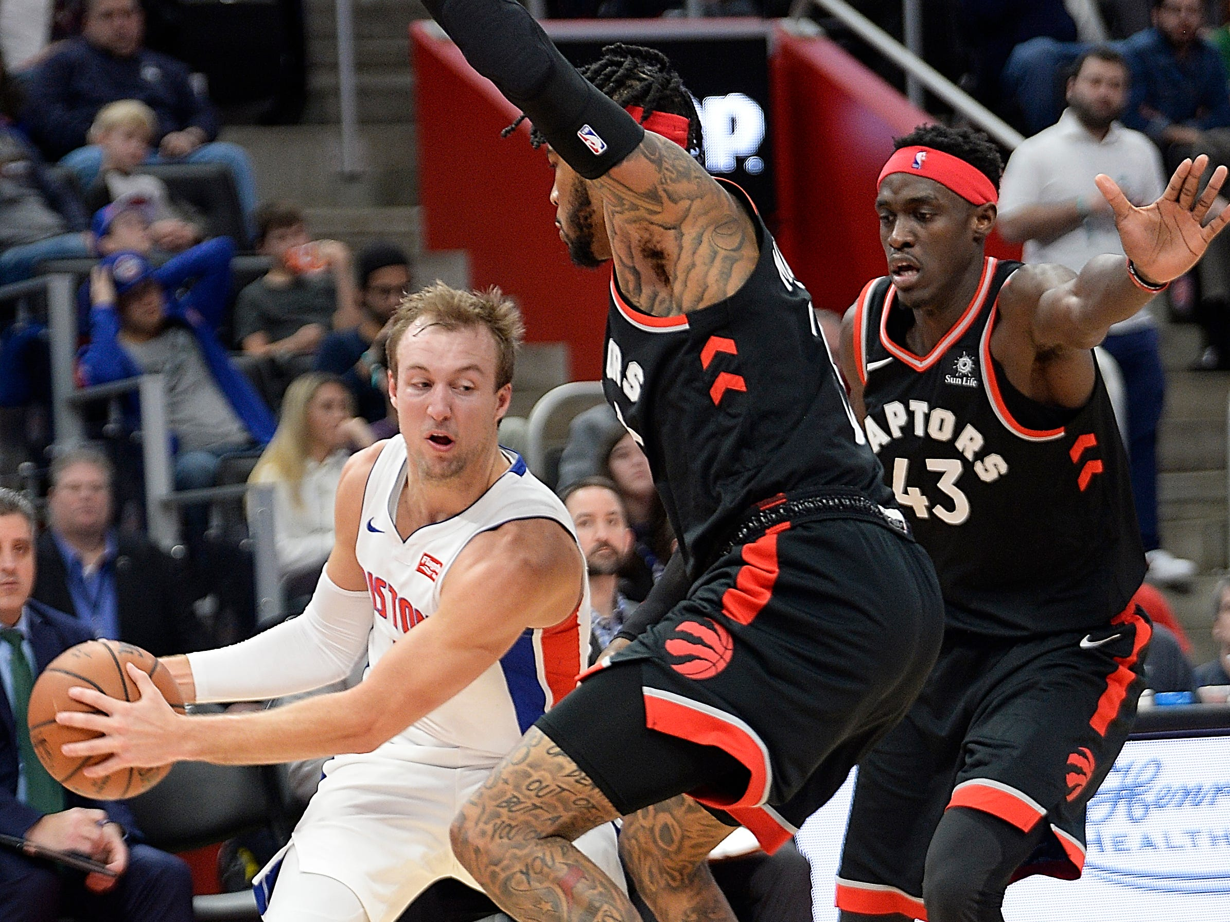 Pistons' Luke Kennard looks for room around Raptors' l-r, Eric Moreland and Pascal Siakam in the fourth quarter.