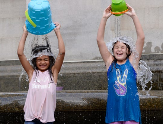Gia Kahan, 8, left, and her sister Leora Kahan, 8, of Huntington Woods play in the water near the Michigan Soldiers and Sailors monument at Campus Martius park on July, 16, 2018.
