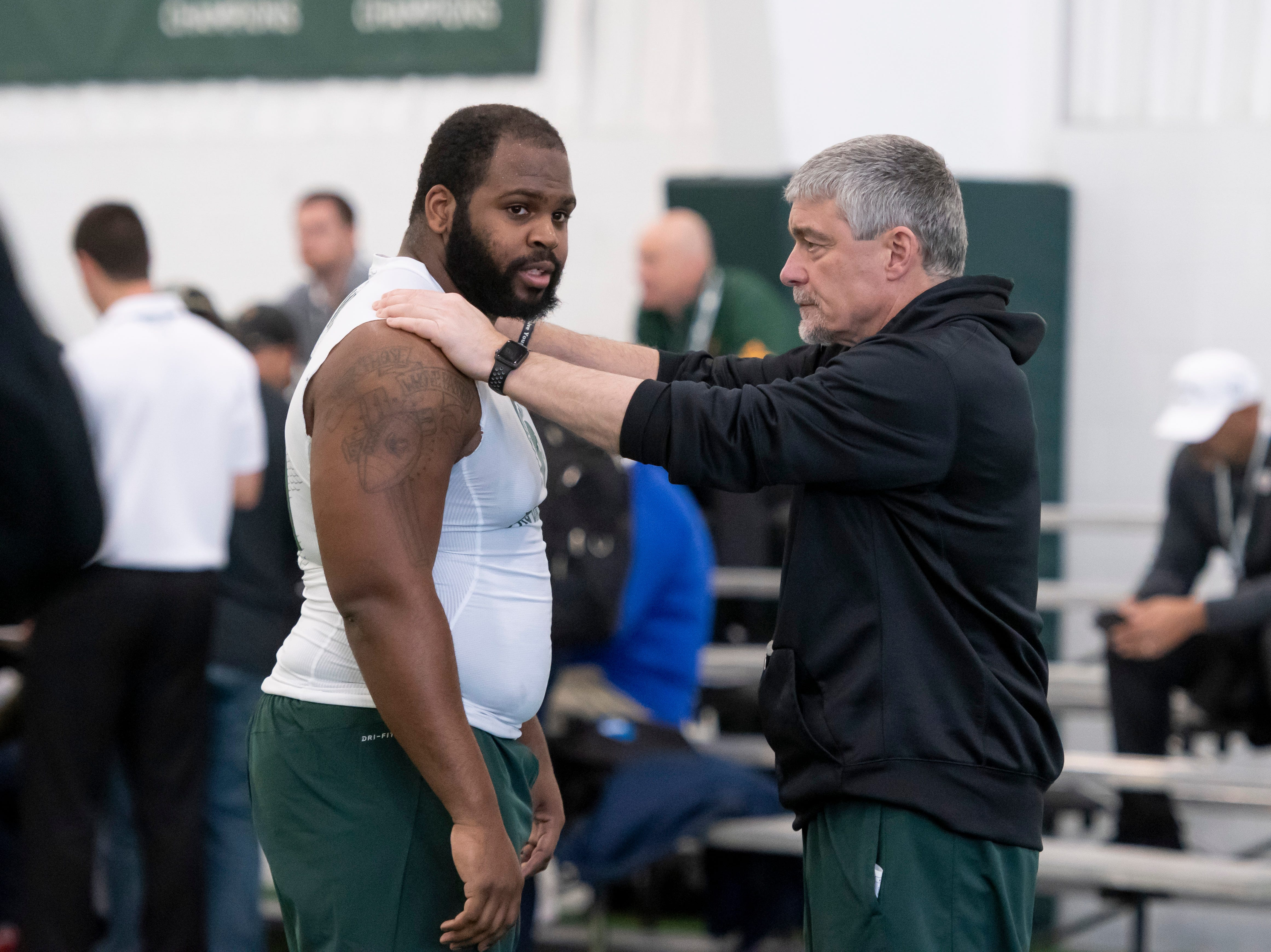 Michigan State head strength and conditioning coach Ken Mannie, right, talks with defensive tackle Gerald Owens during an NFL pro day.