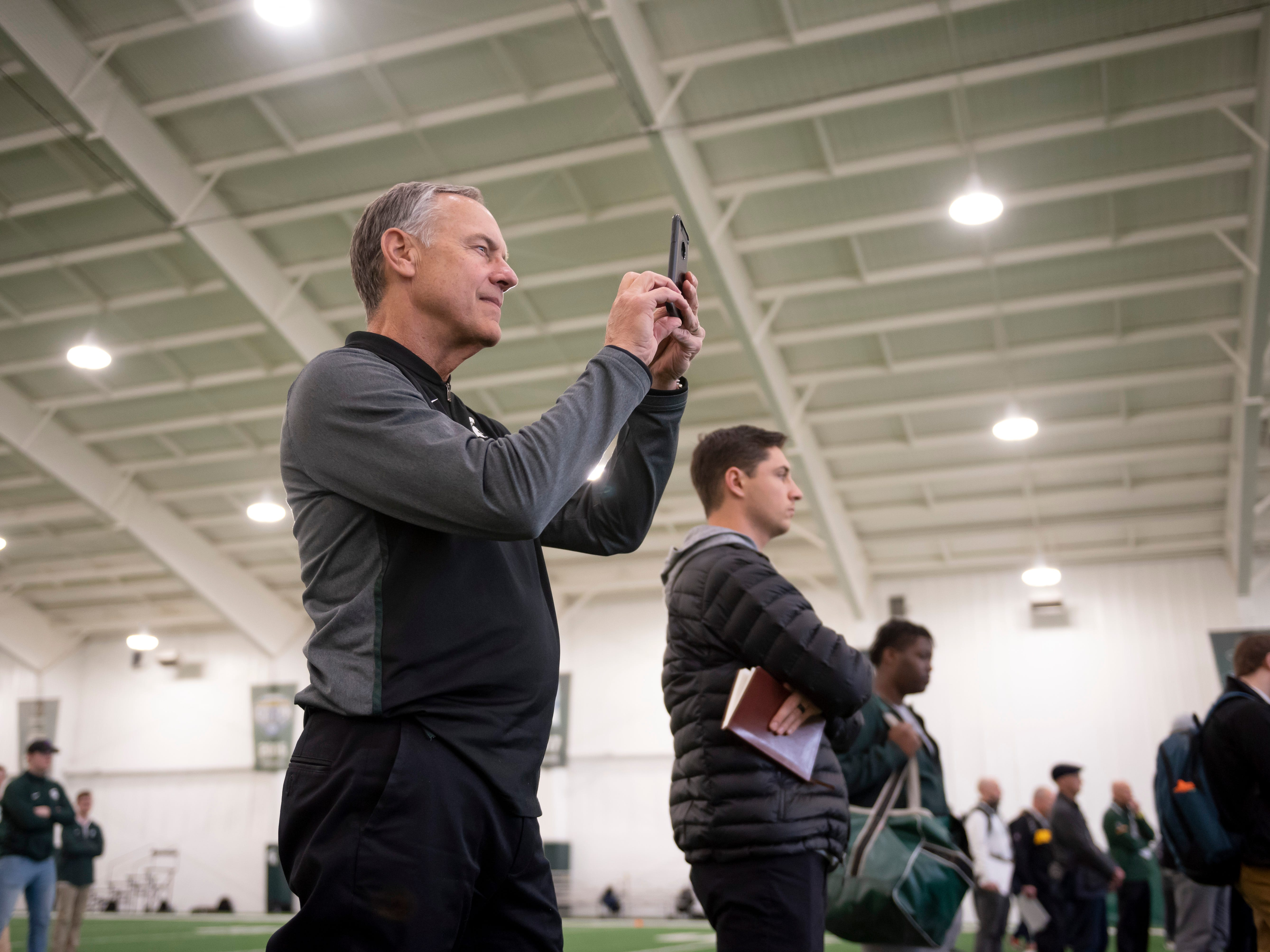Michigan State head coach Mark Dantonio takes photos of his players during an NFL pro day at the Duffy Daugherty Football facility.