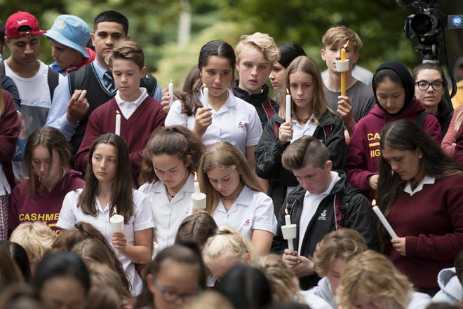 Students hold candles during a moment of silence as they gather for a vigil to commemorate victims of Friday's shooting, outside the Al Noor mosque in Christchurch.