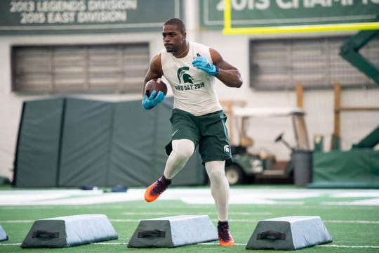 Michigan State running back LJ Scott runs through drills during an NFL pro day.