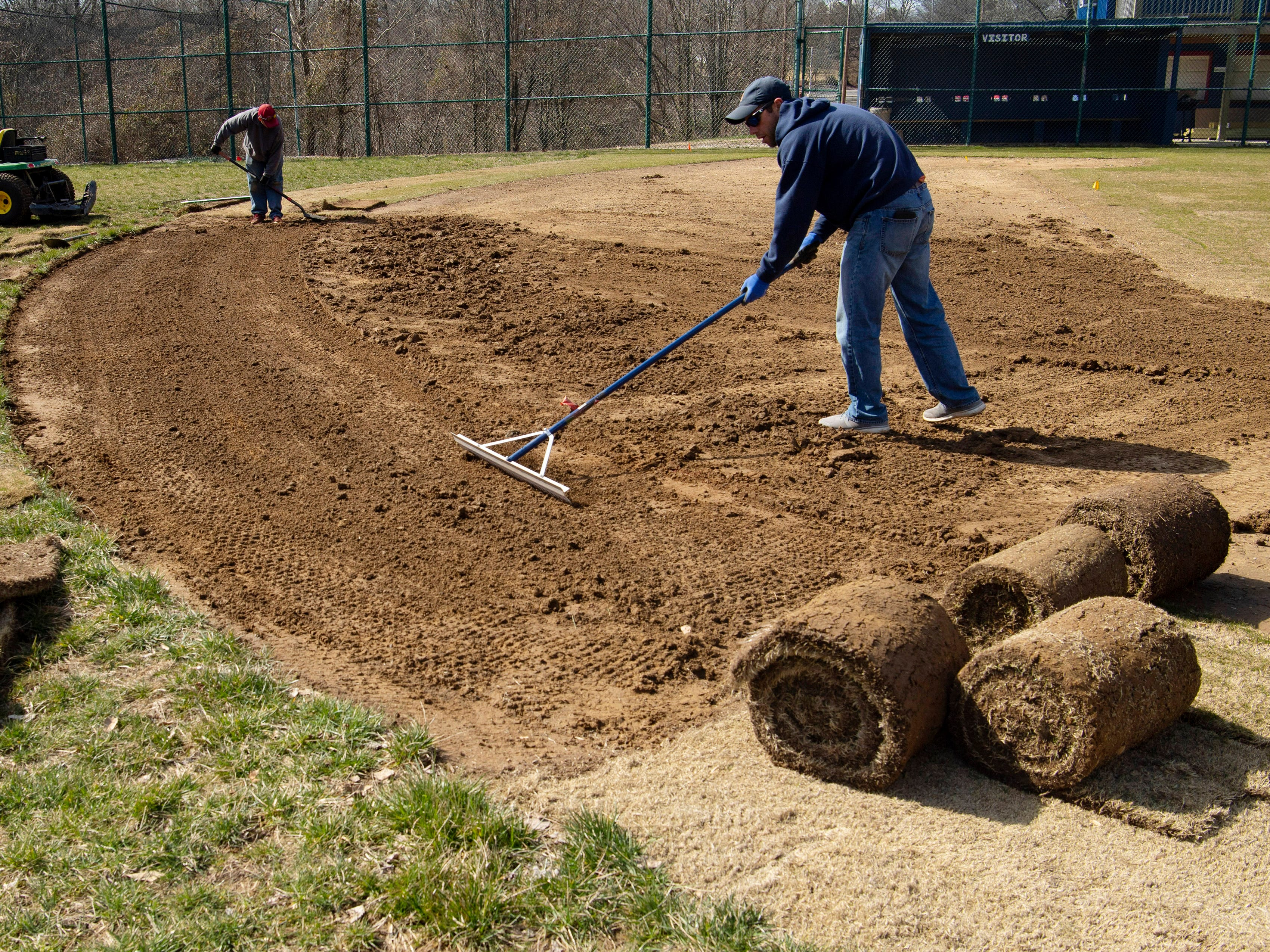 Andy Minnette, right, and Brad Davis level the dirt of the infield at Highland Baseball's Harvey Crow Memorial Field in Evansville Monday afternoon. The Tenbarge Seed Company employees were fixing a spot that had settled behind second base and water was collecting. Minnette said the field would be ready for action this season.