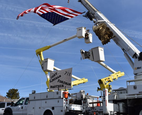 Fort Collins utilities vehicles hoist an American flag above a banner honoring fallen lineman Joe Iglehart on Monday at St. Elizabeth Ann Seton church. Iglehart died of cancer at age 41.