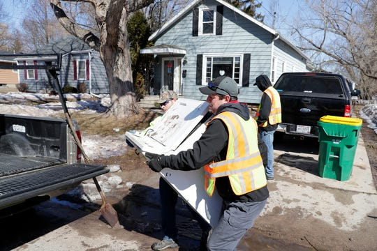Workers clear piles of flood damaged items from outside homes on Eliza St on Monday, March 18, 2019 in Green Bay, Wis.