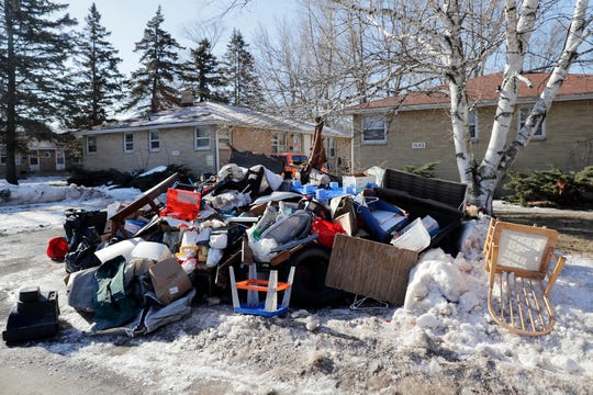A pile of flood damaged items is shown outside residences on Cass St on Monday, March 18, 2019 in Green Bay, Wis.