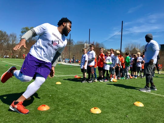 Former Clemson football standout Christian Wilkins demonstrates a cone drill during his youth football camp at Greenville's Kroc Center Sunday afternoon.